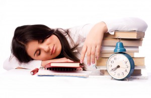 beautiful student falls asleep on the table while preparing for the test